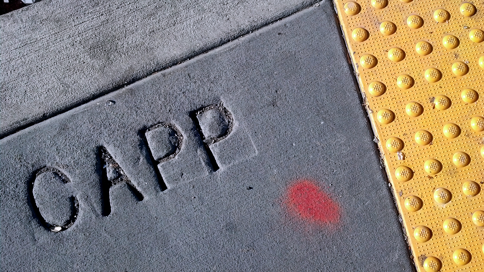 """A close-up of """"Capp"""" written on the sidewalk."""
