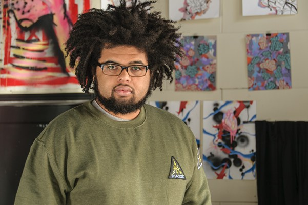 Artist El Chavi stands in front of his paintings displayed at the Faze store.