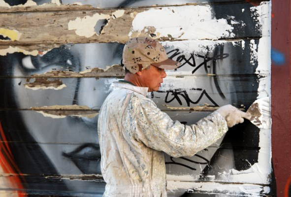 A worker paints over the mural.
