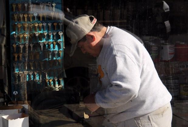 A man cuts keys on Mission Street.