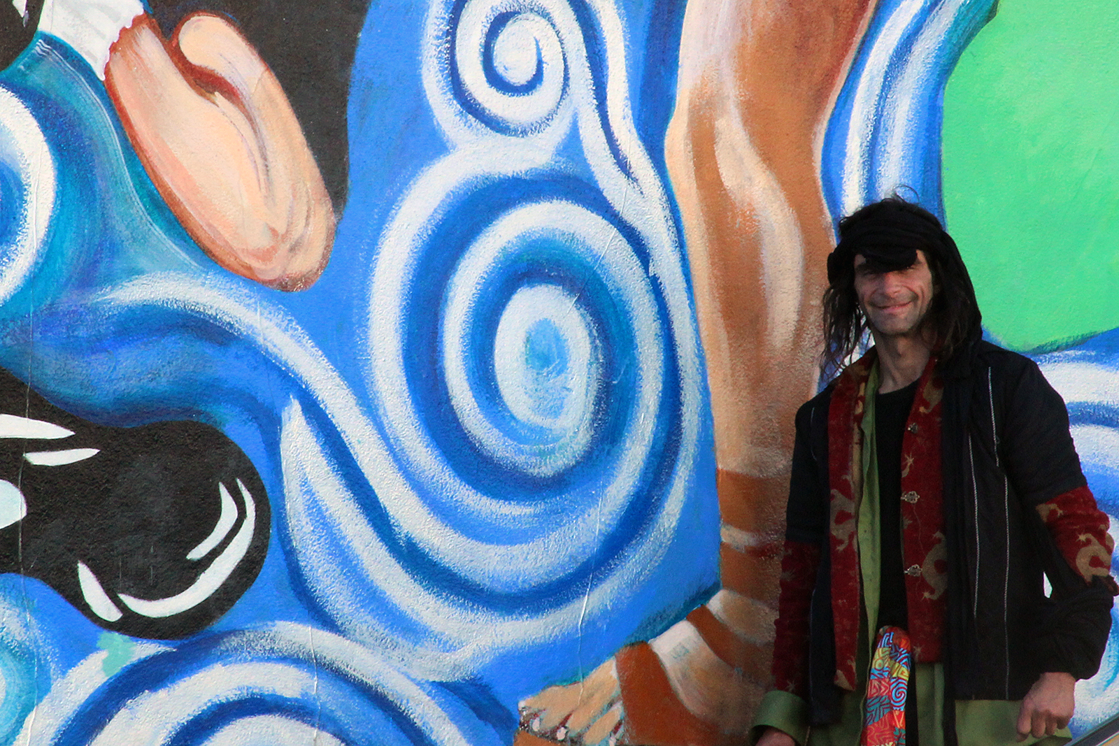 A man stands by a mural near Mission Street.