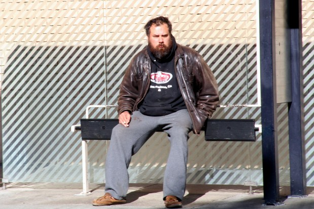 A man waits for the bus on 16th Street.