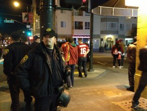 A cop stands ready at 16th and Valencia Streets.