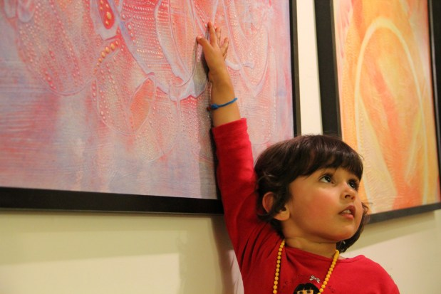 """Sienna Ruman, 3, feels the texture of Brian Grief's untitled piece from his """"Accidental Art"""" collection. """"There's so much texture. They should be able to touch it!"""" says Grief."""