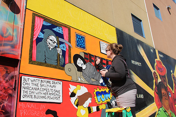 Erin Amelia Ruche works on the mural she and Mike Reger have created in Clarion Alley to raise awareness about the anti-overdose drug Narcan.