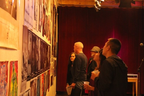 Attendees view the Safe Sex Bang! exhibit, featuring HIV/AIDS prevention posters. Photo by Heather Mack