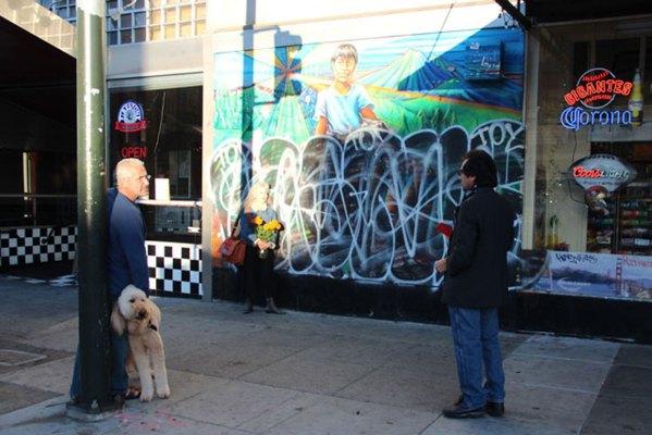 Building owner Nidal Nazzal (far left), muralist Juana Alicia and her husband Tirso talk about restoration on Nov. 2.