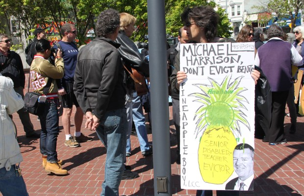A protester holds up a sign demaning that Pineapple Boy LLC rescind the eviction of Benito Santiago.