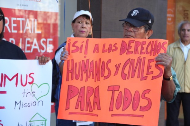 Jesus Sanchaz holds up a sign at Saturday's 'Stop the Flip' rally that reads 'Yes to human and civil rights for all!' Photo by Leslie Nguyen-Okwu.