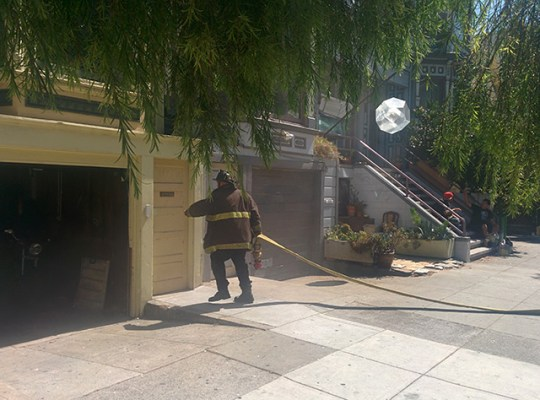 Firefighters are going in through the back on 115 Bartlett Street. Photo by Laura Wenus