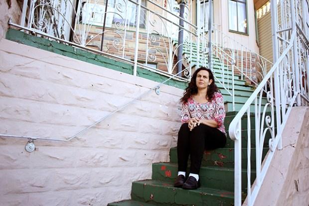 La maestra Tara Ramos sentada afuera de su hogar actual. Un a unidad de una habitación de la cual se suponía iba a mudarse en octubre.