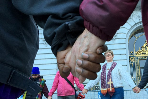 Members of a prayer circle in front of City Hall hold hands on Wednesday evening. Photo by Laura Wenus