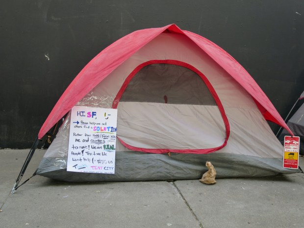 """We are Real people!"" reads a sign posted by a homeless camper on his tent. City officials planned to kick out campers on Division and Bryant streets the next day. Photo by Joe Sciarrillo."