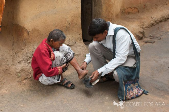 Gospel for Asia-supported pastor helps a leprosy patient.