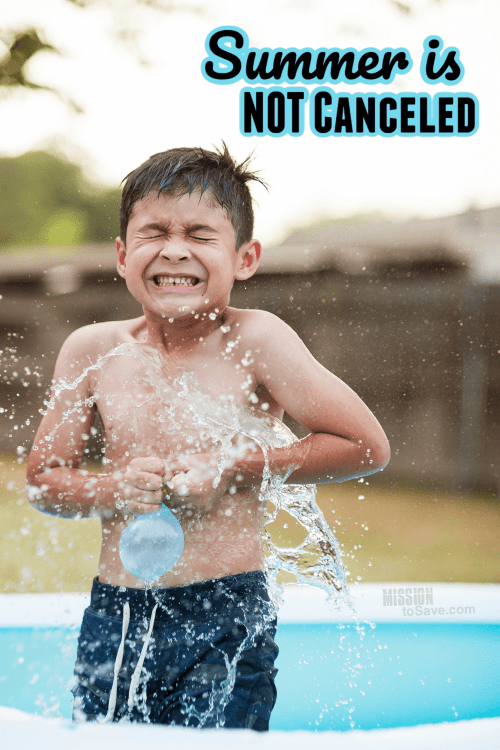 boy playing with water balloon in pool in summer