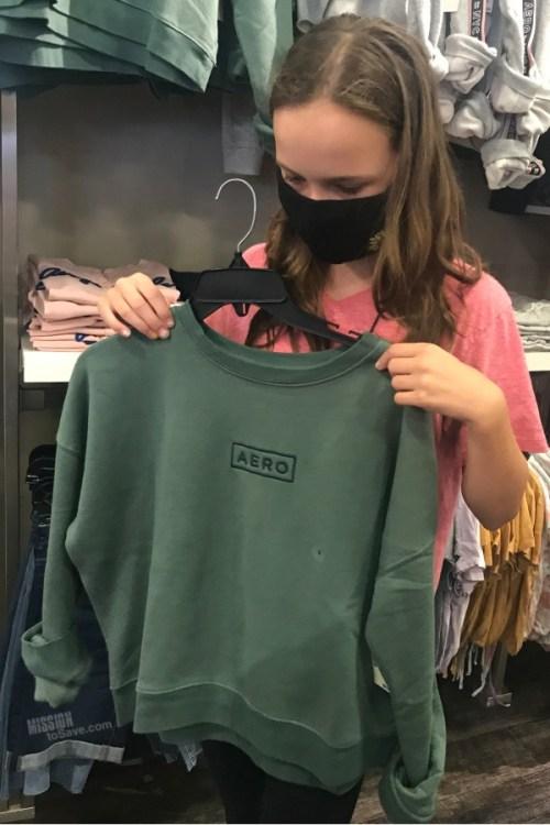 teen girl holding aero sweatshirt