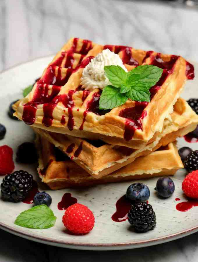 three Belgian waffles with mixed berries, berry puree, whipped cream, and a sprig of mint