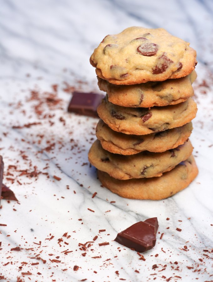six chocolate chip cookies stacked on top of each other on a marble board