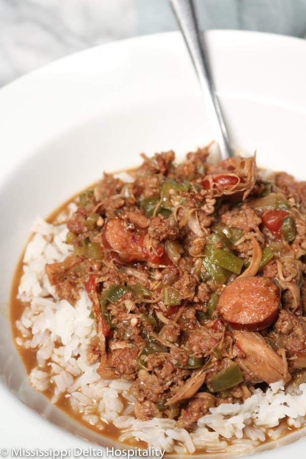 a bowl full of chicken and sausage gumbo with a spoon in it.