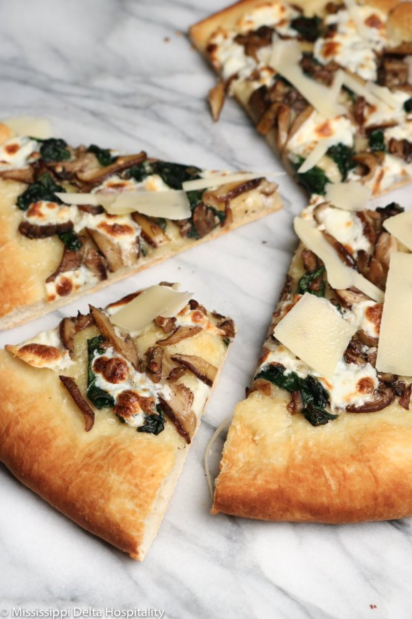 mushroom and spinach pizza on a marble board