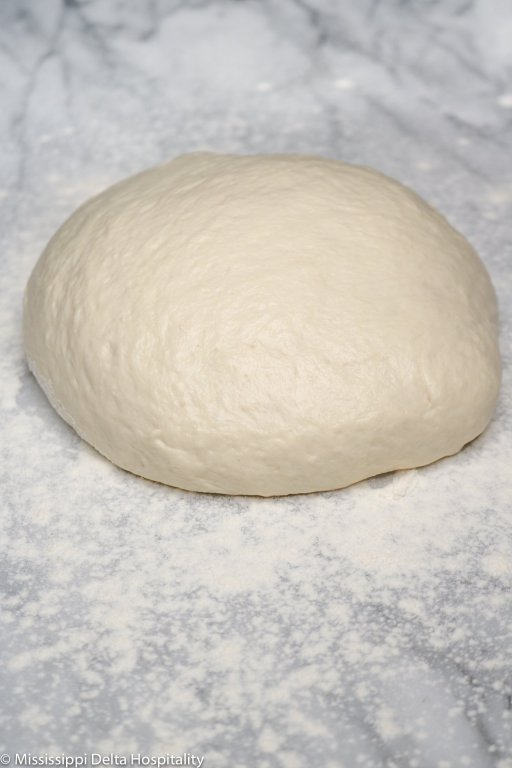 ball of pizza dough on marble board