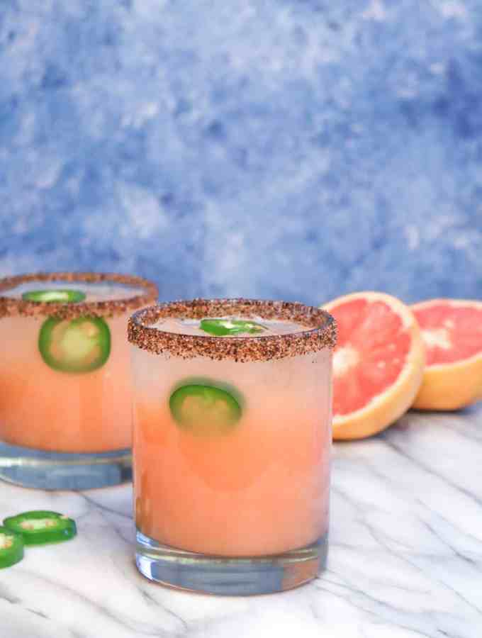 two rocks glasses with spicy grapefruit margarita in them and a chili salted rim on a marble board with jalapeño slices and a grapefruit sliced in half.
