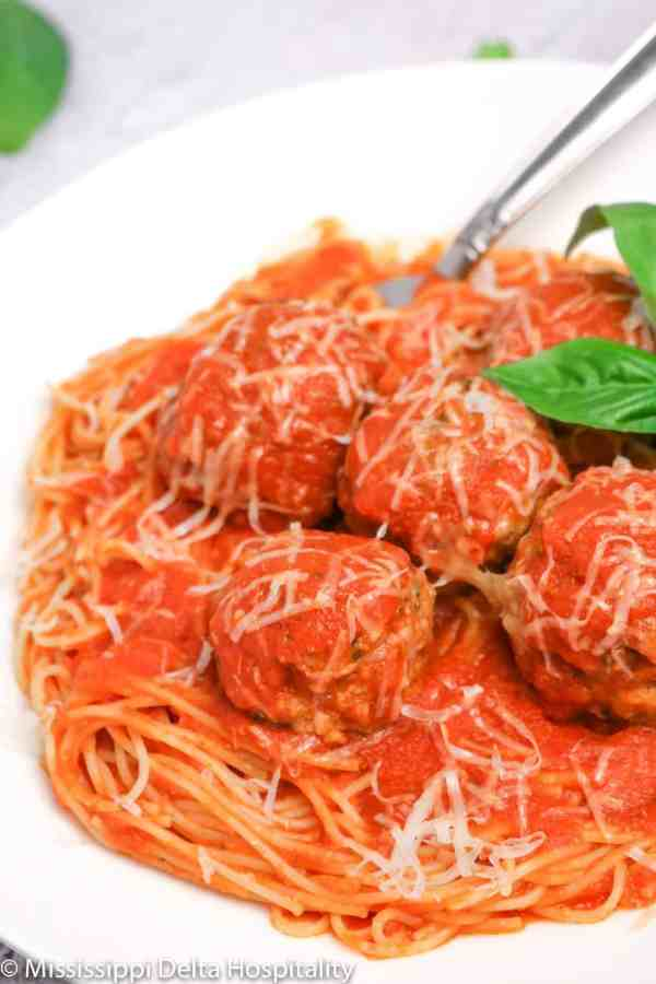 a bowl of spaghetti and meatballs with basil leaves and cheese on top with a fork in it on a concrete board.