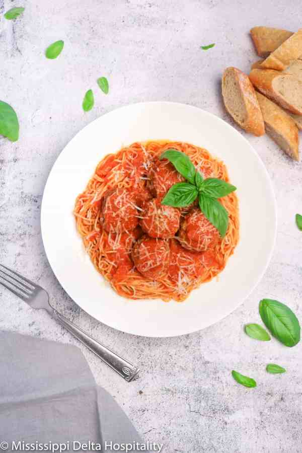 a bowl of spaghetti and meatballs with basil leaves and cheese on top with a fork, a grey napkin, and slices of bread on a concrete board.