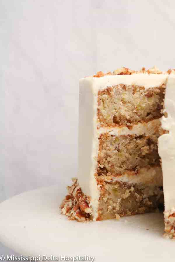 hummingbird cake with a slice missing on a marble cake plate.