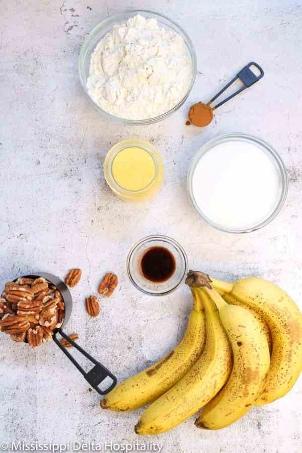 a bunch of bananas, a cup measurement filled with pecans, a glass bowl with vanilla, sugar, and flour with pineapple and cinnamon on a concrete board.