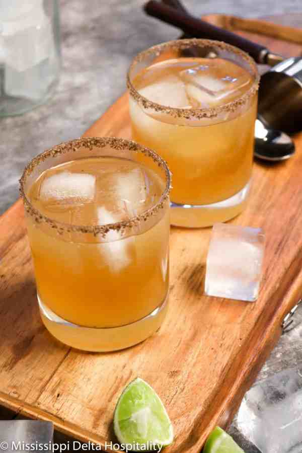 two glasses of margaritas sitting on a wood board with ice and slices of lime along with a stirrer, a jigger on a concrete board.