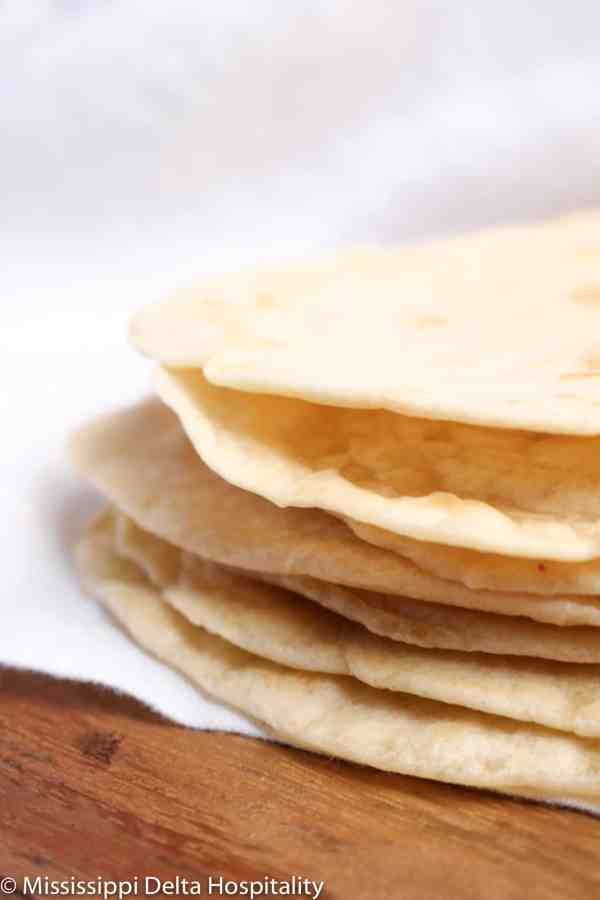 seven flour tortillas on a wood board with a white napkin