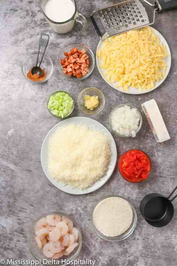ingredients for shrimp and grits on a concrete board.