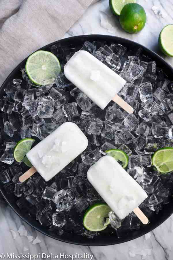 three popsicles on a black serving plate with ice and lime slices on a marble board