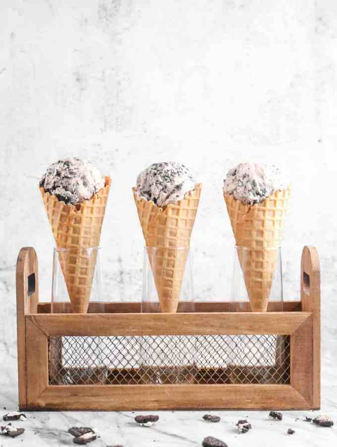 three scoops of ice cream on three waffle cones in a small grate on a marble board