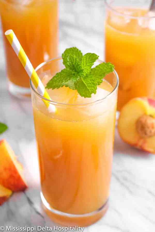 three glasses of peach iced tea with a sprig of mint slices of peach