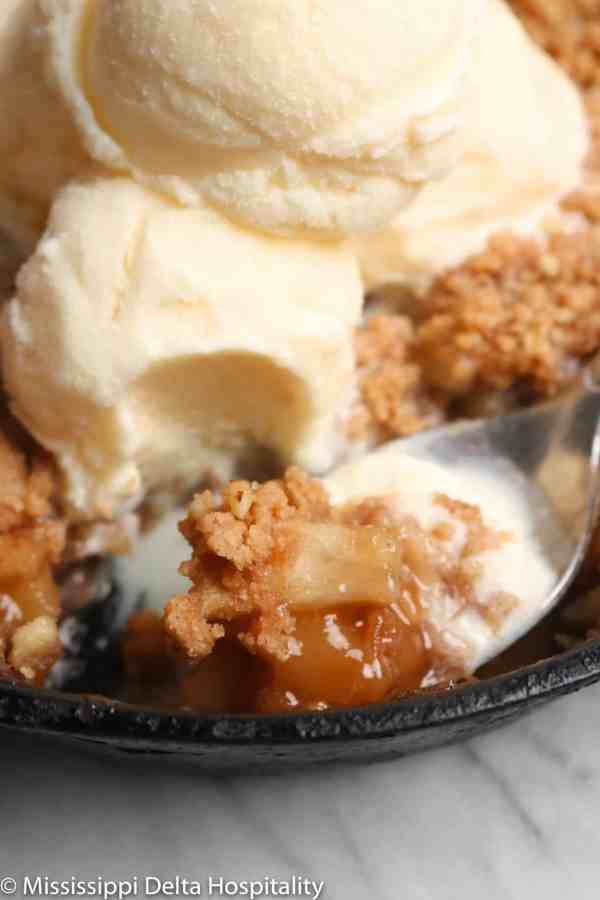 a spoonful of apple crumble in a cast iron skillet