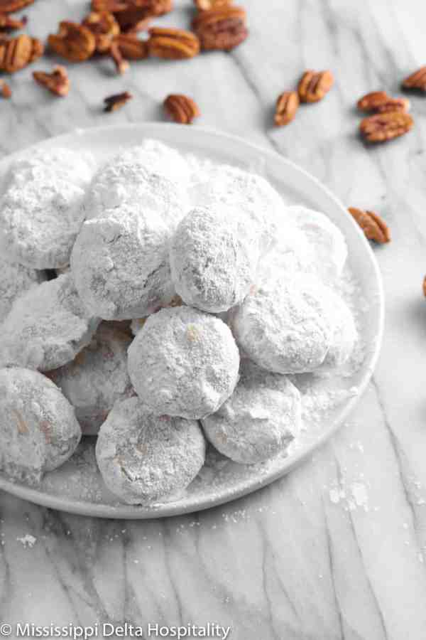 danish wedding cookies piled up on a white plate with pecans in the background