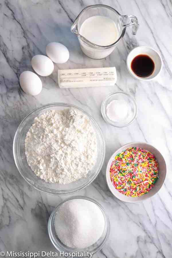 ingredients for a funfetti cake on a marble board