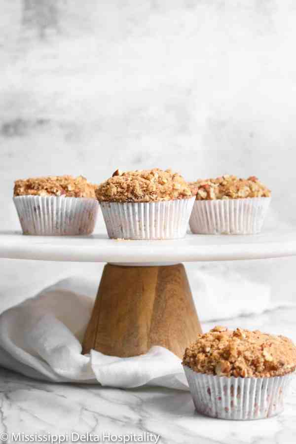 apple cinnamon muffins on a marble cake plate with a white napkin