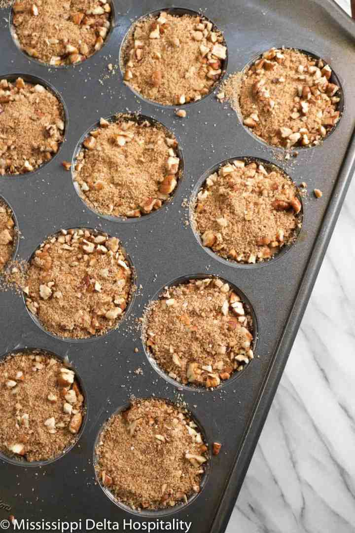 apple cinnamon muffins in a pan with streusel on top