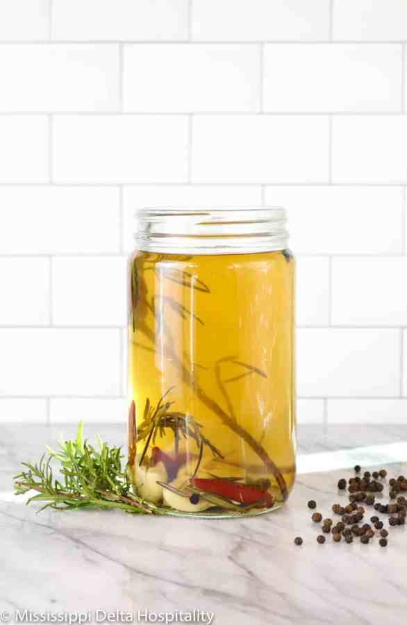 turkey brine in a glass jar with rosemary and peppercorns