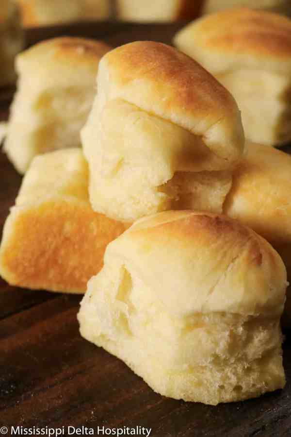dinner rolls stacked on top of each other on a wood board