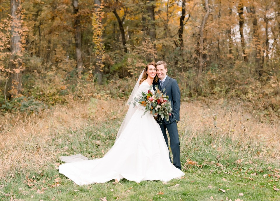 Bride and groom in the fall colors of October at Celebration Farm wedding venue in Iowa City, Iowa