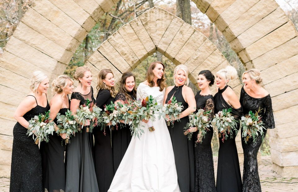 Bridesmaids in black dresses laughing while posing at Celebration Farm in Iowa City