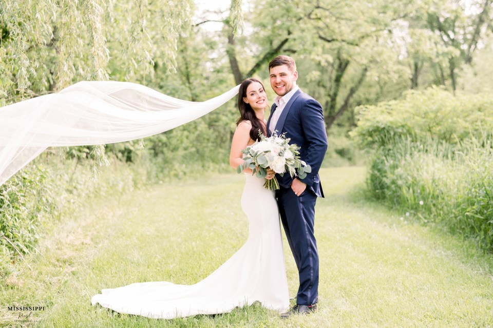 Bride and groom with flowing veil in classic gown