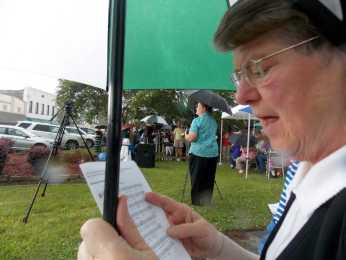 "Sister Judy intently hung onto her umbrella despite the pouring rain and driving wind as we sang ""This Alone""."