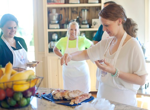 Brandon resident Helen Ann Campbell sprinkles paprika on chicken as fellow students, Ann Marie McGee, far left, and Jennifer Ypya look on Tuesday, June 7, at the Farmer's Table Cooking School in Livingston.