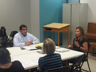 Babak Mostaghimi, school board chair (left), and Kristi Hendrix, executive director of Midtown Partners (right), at the board's June meeting.