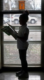 Preschooler Nevaeh Jones is silhouetted against the window as she reads aloud to fellow students at Charleston Elementary.